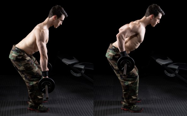 Man in camo pants doing bent-over rows with a barbell against black background.