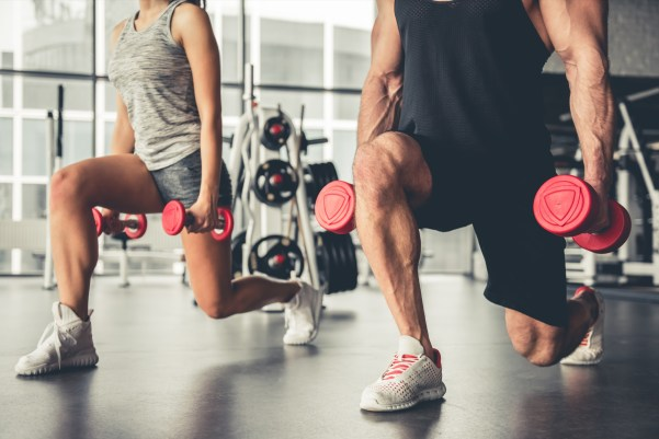 Man and woman lunging in gym with dumbbells in hand.