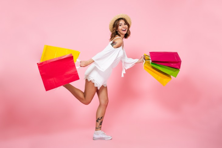 happy pretty girl holding shopping bags while running and looking at camera isolated over pink background