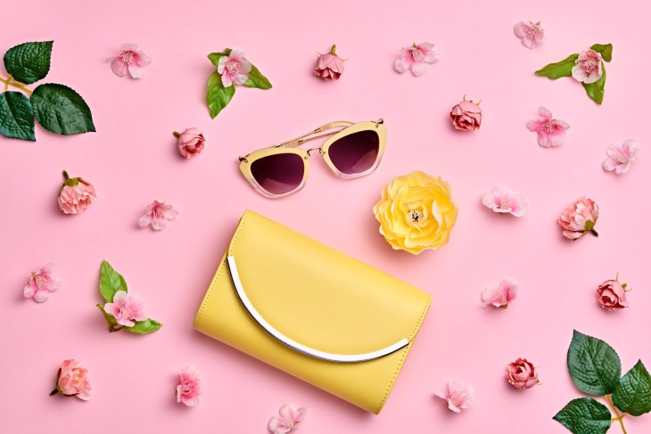Fashion Woman Accessories Set. Pink Pastel Color. Flat lay. Minimal Style. Trendy Yellow Clutch, Glamour Summer Sunglasses. Roses Flowers. Spring Floral
