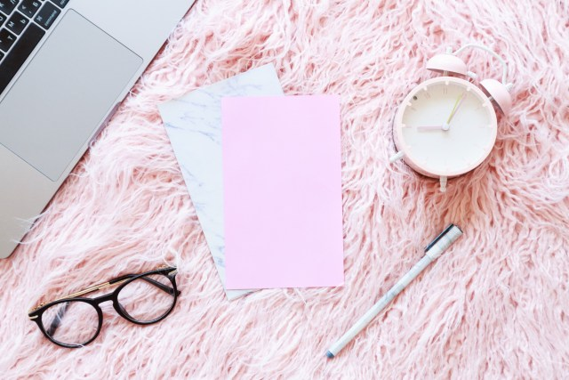 Flatlay of laptop, women knitted sweater, reading glasses, paper, pen, alarm clock on a pink fur background