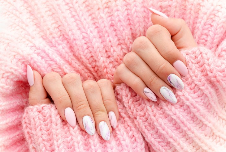 Female hands manicure close up view on pink knitted sweater background. Nail painting effects