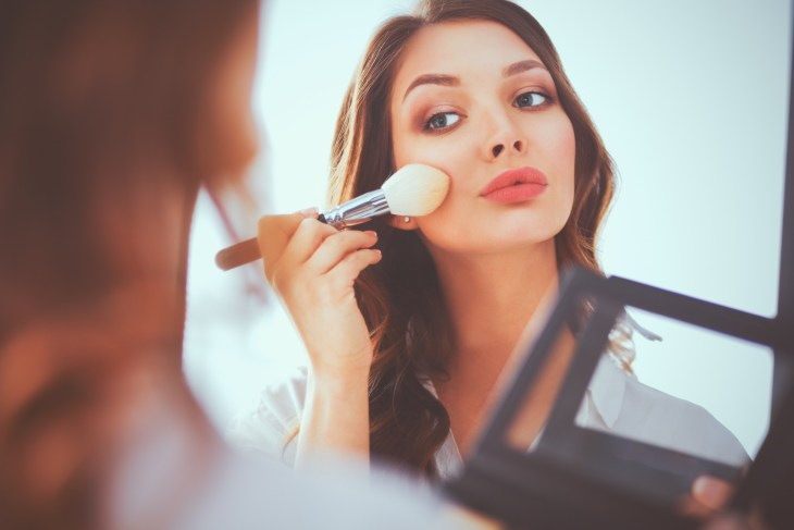 Young beautiful woman making doing her make-up near a mirror