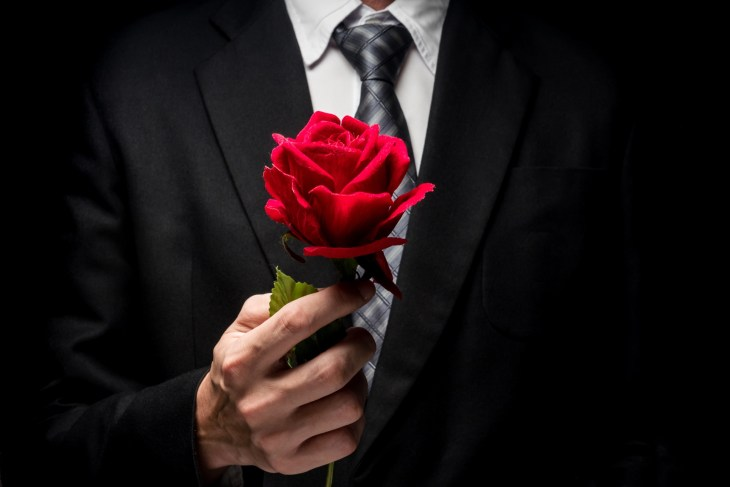 Man In Suit Holding Red Rose