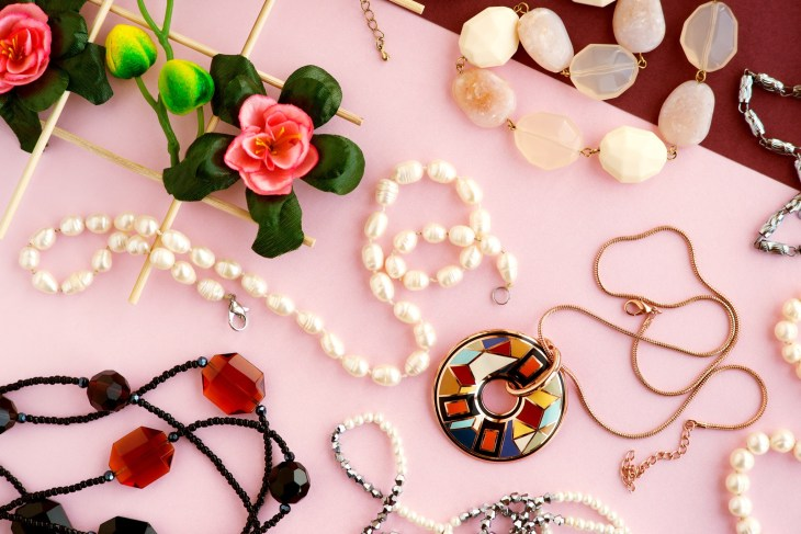 Display Of Jewelry Against Pink Back Drop With Flower