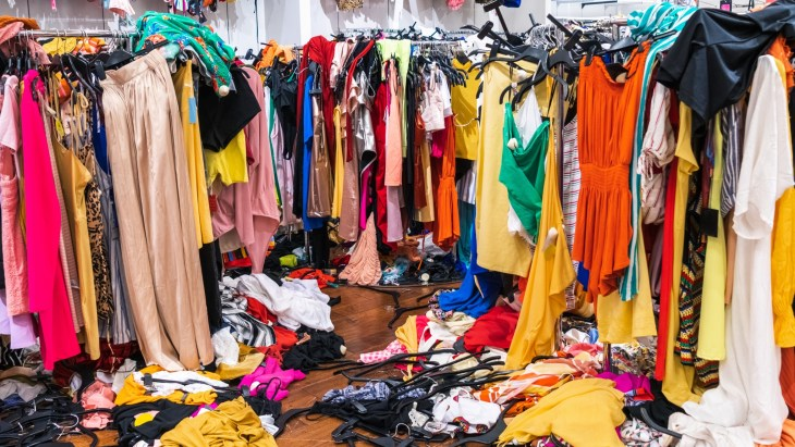 Fast Fashion Store With Overstocked Clothes Hanging Off Of Racks