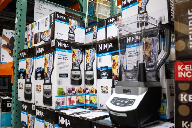 Many ninja blenders in boxes stacked on top of each other.