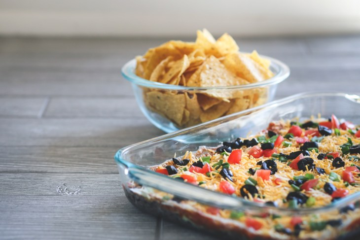 A seven layer dip next to a bowl of tortilla chips.