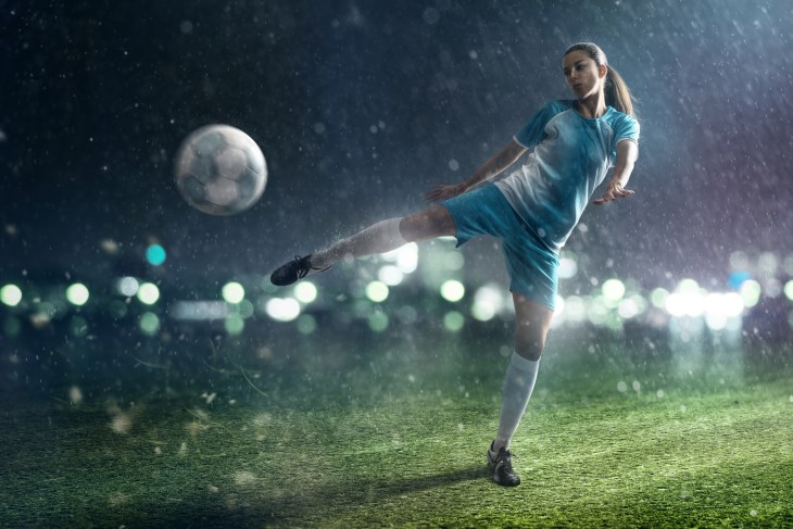 A woman playing soccer at night in the rain.