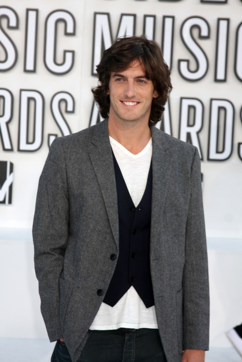 Photo of William Tell in front of white Music Awards background with long hair and grey blaiser.