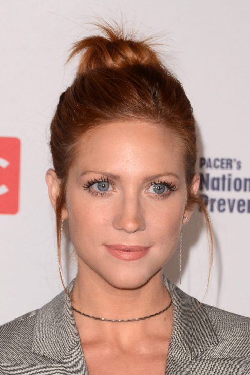 Photo of Brittany Snow with orange red hair with a bun and grey blaiser on.