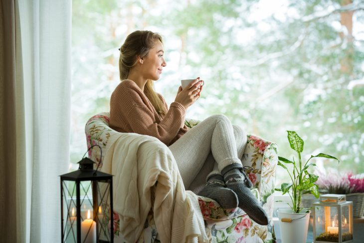 A woman sitting on a chair with a cup of tea.
