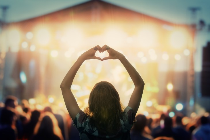 A girl is facing a stage and is in the center of the crowd. She is attending a concert with her arms held above her head and her hands in shape of a heart. The crowd and stage is blurry to focus on her.
