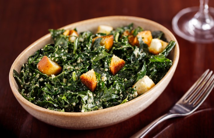 Kale caesar salad with croutons in a white bowl.
