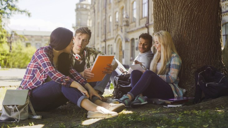 A woman, man, another man and another woman sitting in a circle outside with a notebook.