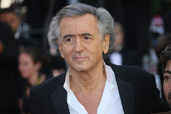 Bernard Henri Levy wearing black suit with white unbuttoned shirt looking off into the distance with blurred out people in the background wearing formal attire.