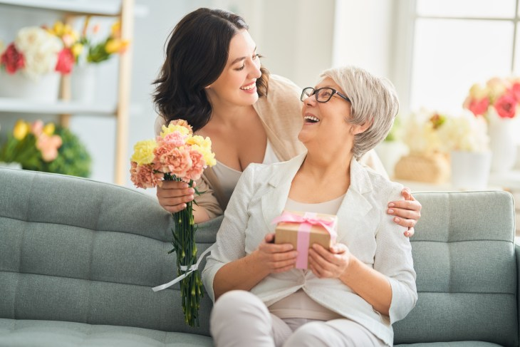 Beautiful young woman and her mother with flowers and gift box at home.