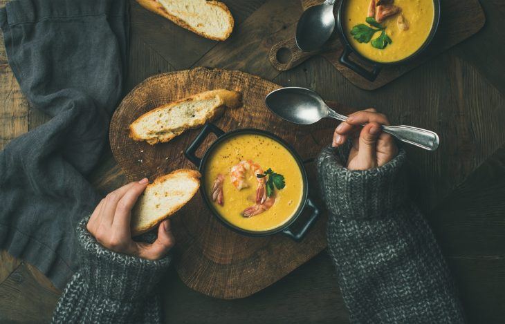 Hands holding a piece of bread and reaching into a bowl of soup.