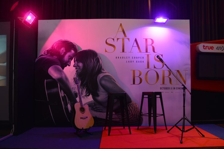 """A small stage lit with a backdrop of the cover photo of """"A Star Is Born""""."""