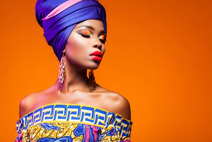 African woman in brightly colored dress and headwrap on orange background