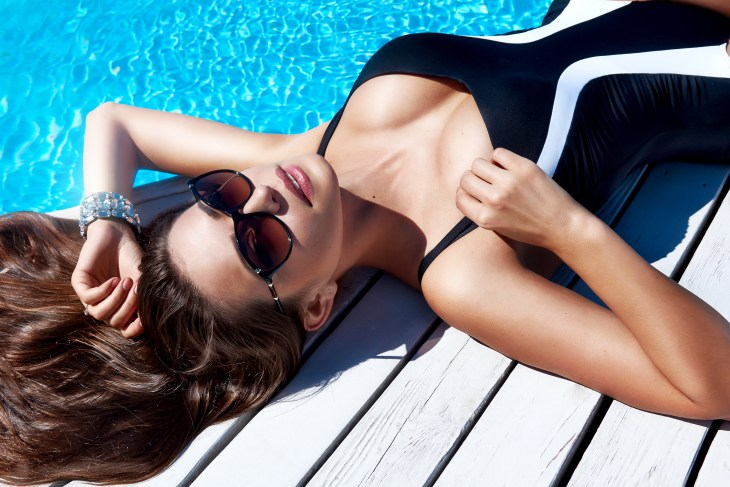 Beautiful woman wearing sunglasses and a one piece swim suit sitting next to the pool
