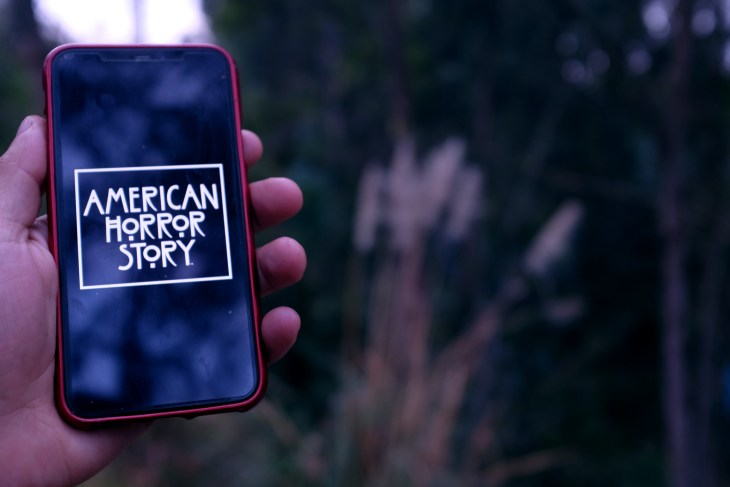 """""""American Horror Story"""" logo on phone that is being held by someone"""