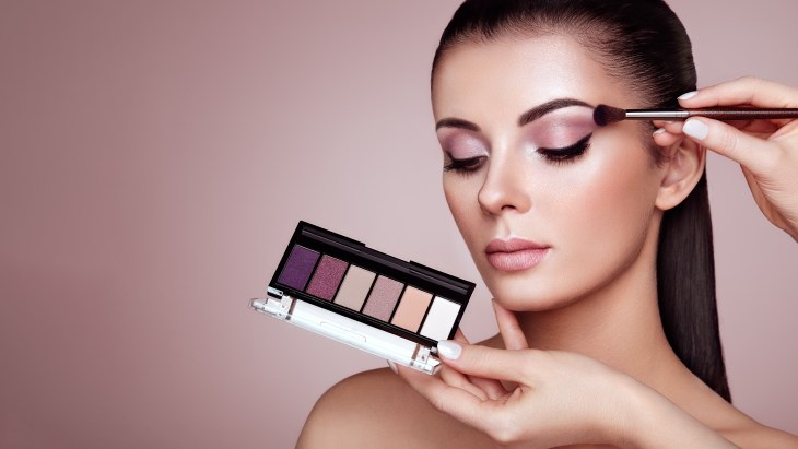 Makeup artist applying pinkish purple eyeshadow to beautiful young woman with dark hair and tan complexion