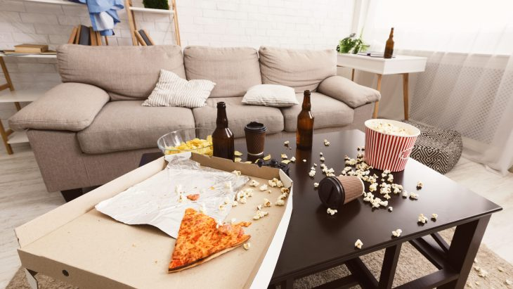 messy college apartment coffee table with beer bottles, popcorn, and pizza all over the table