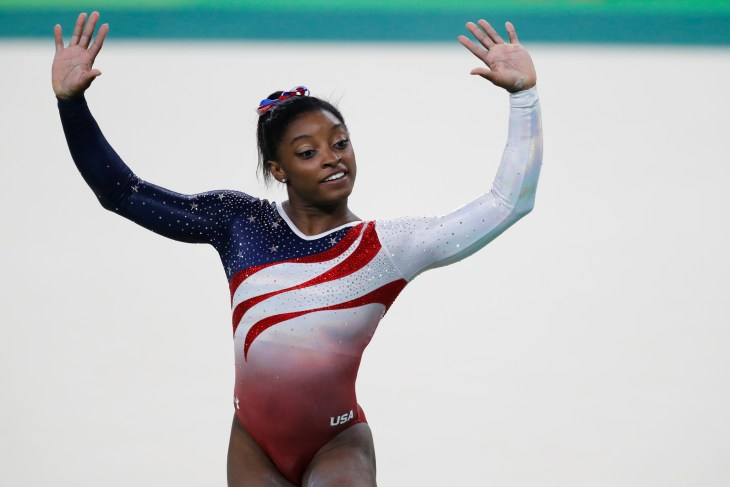Simone Biles with her arms up
