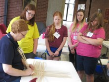Students watch as their Instructor shares some basket weaving techniques.