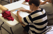 A student working on his own self-portrait.