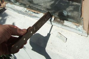 Removing the putty on an old piece of glazing. (Photo by Andy Dingley.)