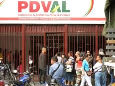Decenas de personas hacen fila afuera de un mercado subsidiado del gobierno (PSVAL) para adquirir productos como carne de pollo, harina, leche y papel higiénico, todo de forma racionada