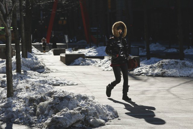 A woman walks during low temperature at Lower Manhattan in New York, February 20, 2015. Millions of people awoke to painfully cold weather in the eastern United States on Friday, with temperatures frigid enough in New York City and Washington to break decades-old record lows for Feb. 20. REUTERS/Eduardo Munoz (UNITED STATES - Tags: ENVIRONMENT)