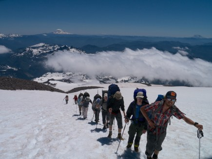 Andy leading the group up the Muir snowfield. Mt Adams, Mt Hood, and Mt St Helens are visible in the backgrouhnd
