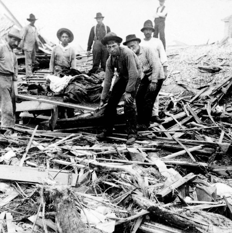 Men cleaning up rumble from the 1900 Galveston hurricane. In black and white.