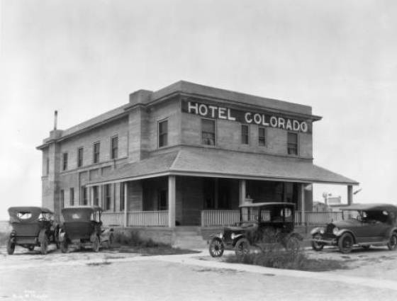 Arriba - Two- story Hotel Colorado is a flat-roofed plain stone block structure with a covered veranda along front facade, 1919.