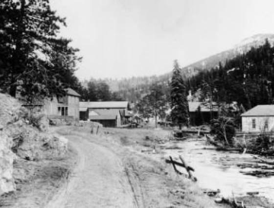 Evergreen - View of Amos Post's trading post on road running between a rock outcropping and frozen Bear Creek, 1900-1910