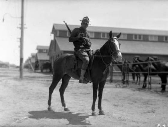 A mounted cavalry soldier poses while pouring tobacco into his rolling paper, outside a row of stables - 1917-1918.