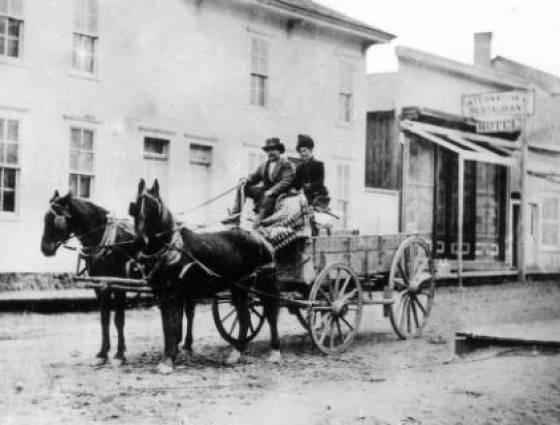 X-21793 Couple in wagon - sign reads International Restaurant & Hotel, 1880s.