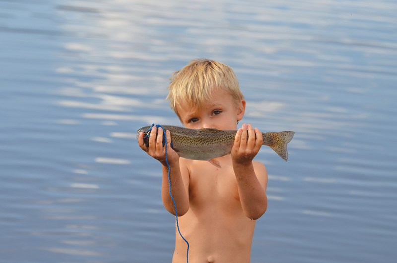 A boy's smile hides behind a rainbow trout at Steamboat Lake State Park