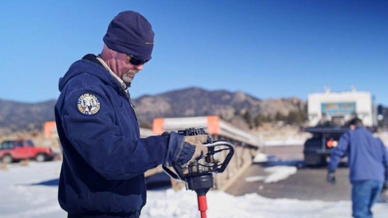 Hatchery Technician Mark Haver drills through rock-hard ice