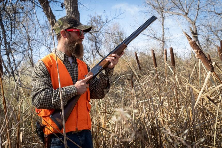 hunter holding shotgun in ready position.