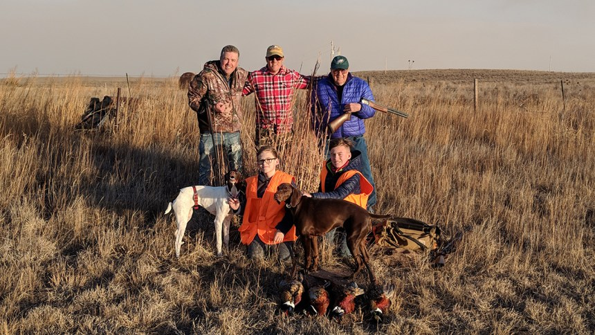 Three generations of hunters enjoy a day of pheasant hunting.