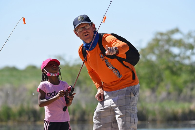 Travis Duncan, CPW Statewide Public Information Officer, helps first-time angler Rise Hammons, 6, learn to cast.