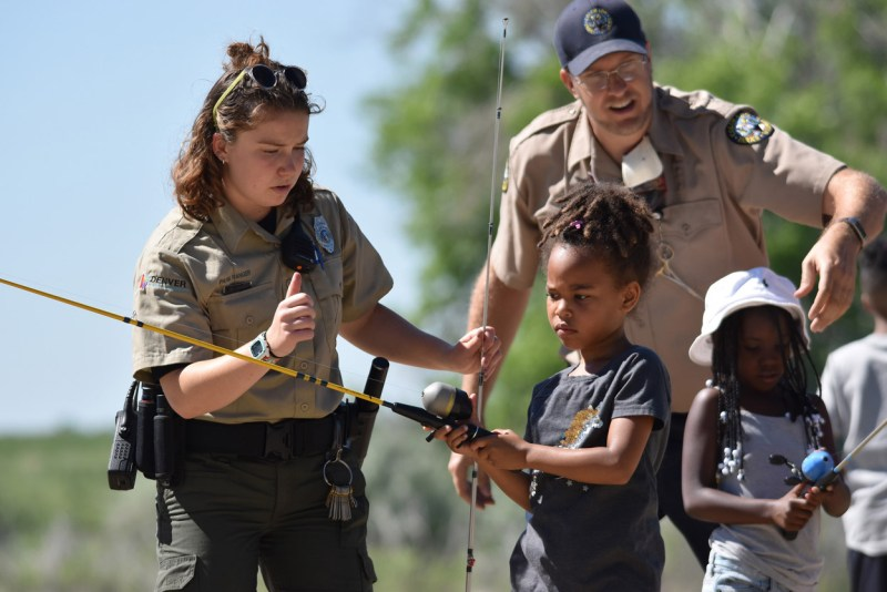 Colorado Parks and Wildlife and Denver Parks and Rec staff distribute free fishing poles.