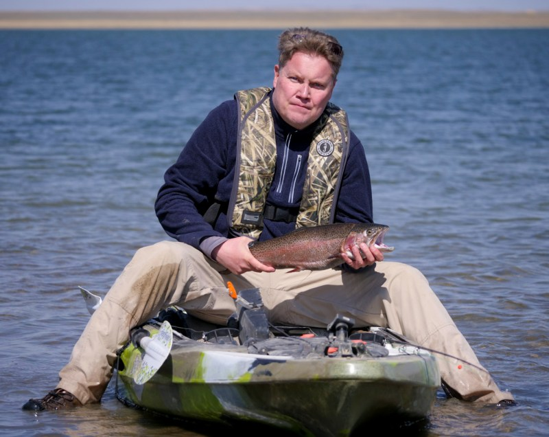 author poses with a nice trout caught from his kayak