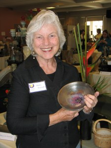 Marta holding one of her pots at the Colorado Potters Show