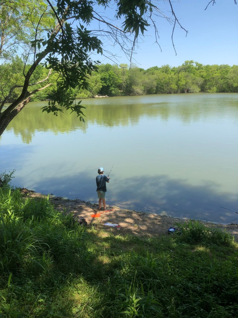Boy fishing at pond in Wells Branch Hike and Bike Trail in north Austin