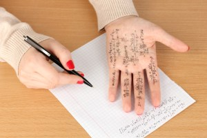 Hand with cheat sheet written on it